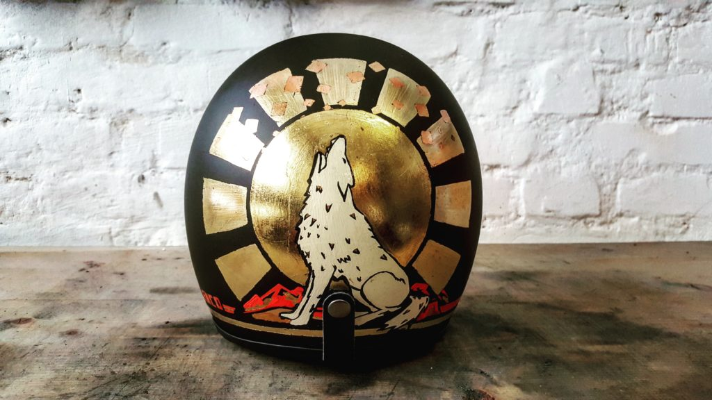 Custom motorcycle helmet with gold and a wolf